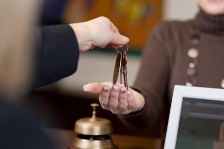 Recepcionista dar las llaves a los clientes en la recepción en el hotel Foto de archivo