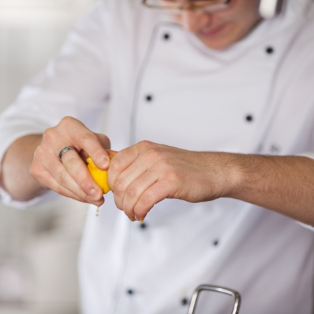 Closeup of chef's hands squeezing lime in commercial kitchen photo