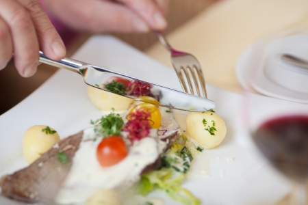 knife tomato: Closeup of mans hands holding fork and knife to cut potato at restaurant table