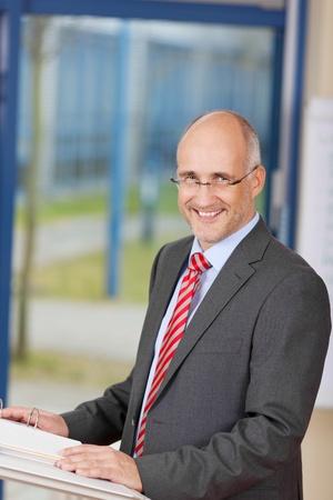 hablar en publico: Sonriendo maduro hombre de negocios de pie en el podio en la oficina