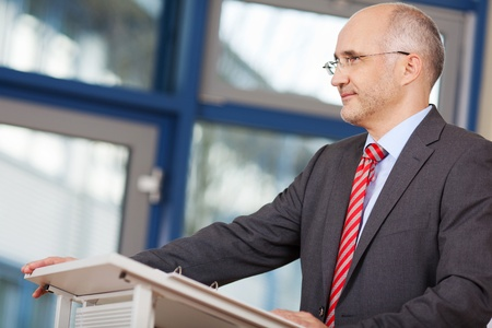 Confident mature businessman looking away while standing at podium in office photo