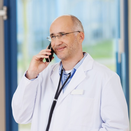 conversing: Confident male doctor conversing on cordless phone in clinic Stock Photo