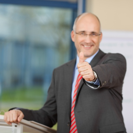 Portrait of confident businessman showing thumbs up sign at podium in office photo