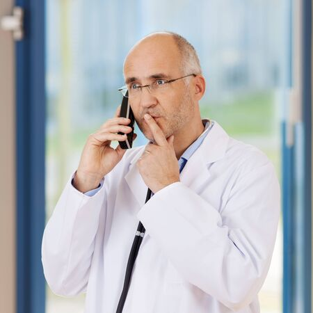 Mature male doctor using mobile phone while holding finger on lips Stock Photo - 21217157