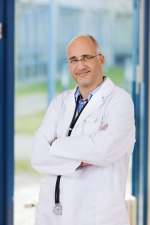 folded hands: Portrait of confident male doctor with arms crossed standing in office Stock Photo