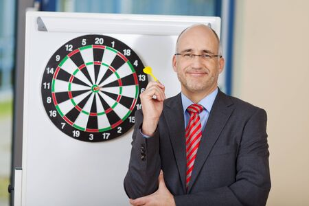 attaching: Portrait of mature businessman attaching dart on target Stock Photo