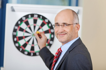 attaching: Portrait of mature businessman attaching dart on target in office