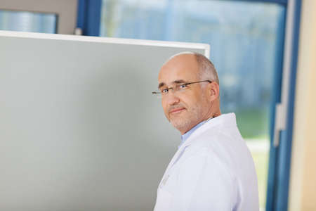 Thoughtful mature male doctor with hand on flipchart in clinic photo