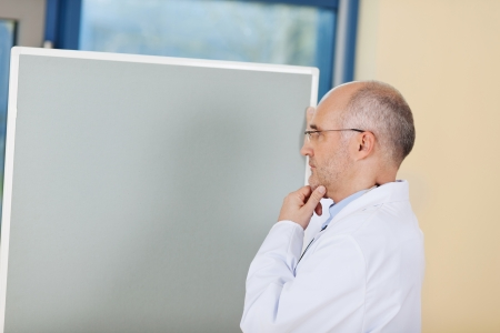 Thoughtful mature male doctor with hand on chin standing by flipchart in clinic photo