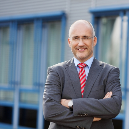 business building: Portrait of confident businessman with arms crossed standing against building Stock Photo
