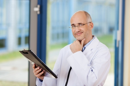 consultant physicians: Thoughtful male doctor with hand on chin looking at camera Stock Photo