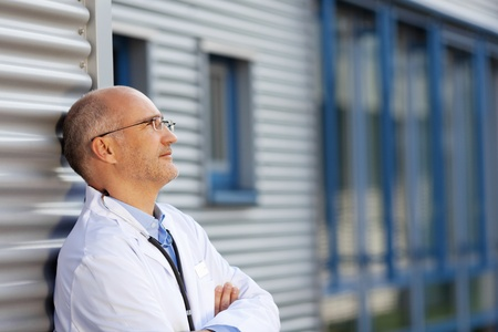 Thoughtful mature doctor leaning on wall while looking away photo