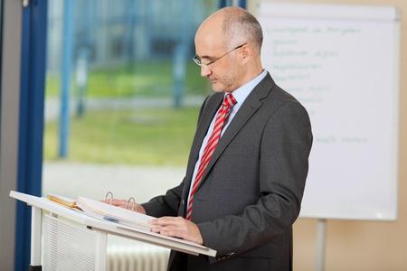 hablar en publico: Retrato de confianza lectura negocios maduro en el podio en la oficina