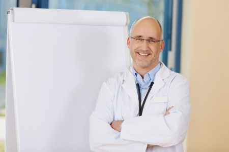 medical education: Portrait of confident mature doctor with arms crossed standing by flipchart in clinic Stock Photo