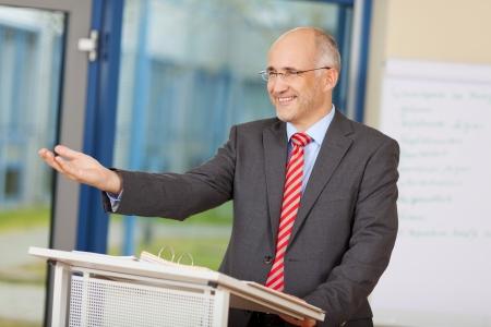 オフィスで表彰台に立っている身振りで示す幸せな成熟した実業家