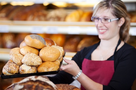breadloaf: saleswoman holding a tray of bread rolls in bakery