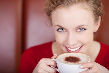 coffeeshop: smiling, beautiful woman drinking cappuccino in a coffee shop