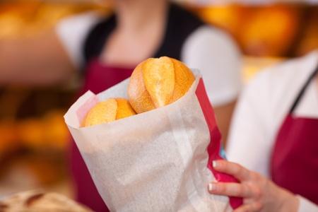 bolsa de pan: Detalle de trabajador panadería bolso femenino que sostiene de panes
