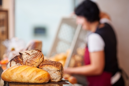 unhealthful: Closeup of bread loafs on counter with woman empting create in background at bakery