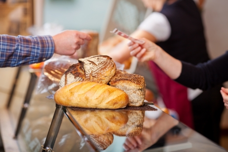 breadloaf: Closeup of customer paying for breads at bakery counter