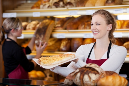 saleswomen: smiling young woman selling cake in bakery