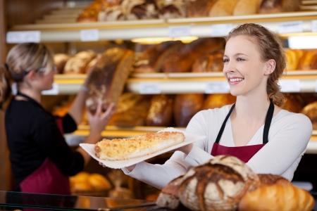 contadores: sonriente joven vende la torta en la panader�a Foto de archivo