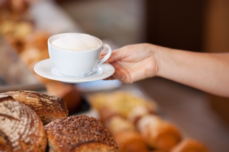 breadloaf: Closeup female bakery worker serving cappuccino