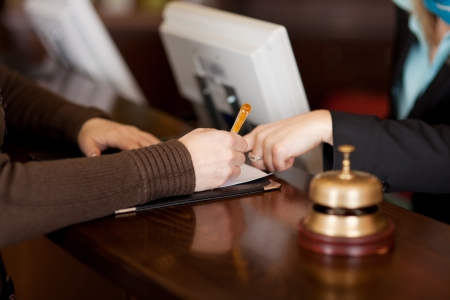 hotel booking: Closeup of receptionists assisting female customer in filling up form in hotel Stock Photo
