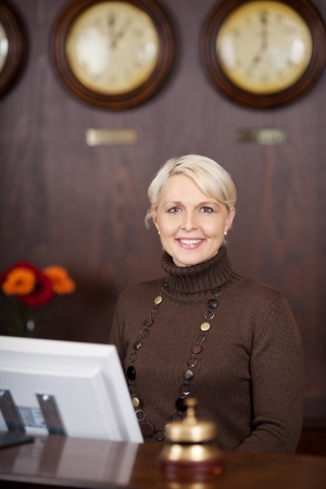 confident female receptionist behind the hotel counter photo
