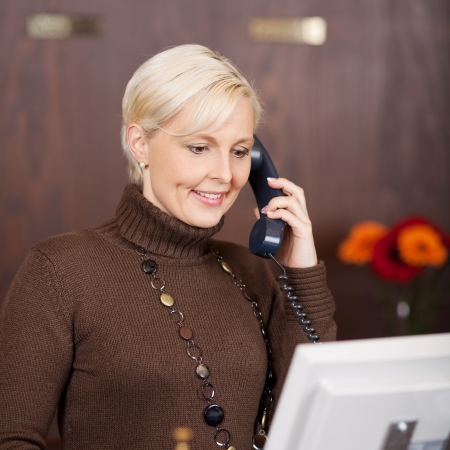 to attend: portrait of a cheerful female receptionist using telephone