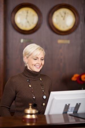 attend: smiling female receptionist working at hotel counter Stock Photo