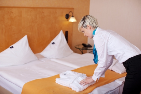 hotel service: Side view of young female housekeeper keeping bathrobe on bed in hotel Stock Photo