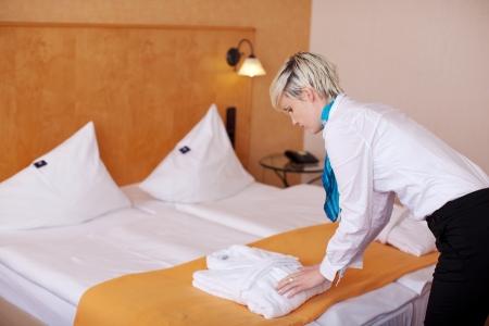 Vue latérale de la jeune femme de ménage féminin gardant peignoir sur le lit à l'hôtel