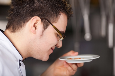 commercial kitchen: Closeup of young chef smelling dish in commercial kitchen