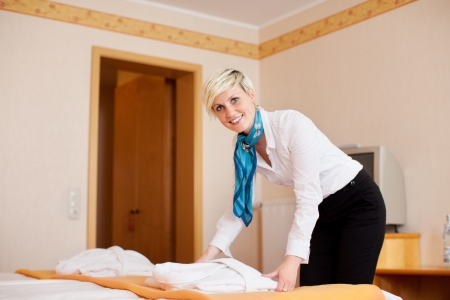 Portrait of young female housekeeper keeping bathrobe on bed in hotel photo