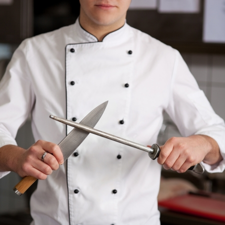young knife: Male chef sharpening knife in commercial kitchen