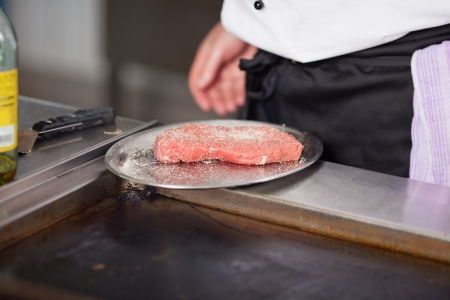 cook with raw meat in restaurant´s kitchen photo