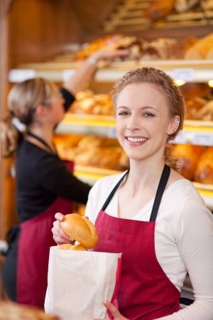salesgirl: Portrait of happy female worker packing breads in bakery