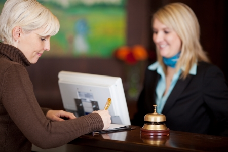 checkout counter: female guest filling up a formular at hotel counter