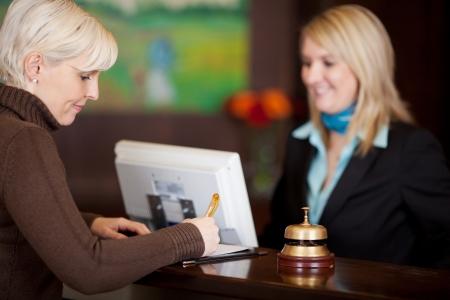 contadores: invitada llenar un Formulario en el mostrador del hotel