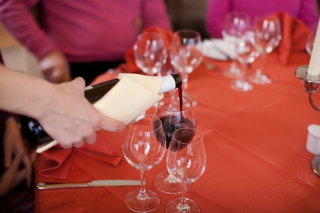 Closeup of waitress hands pouring red wine in glass for customers at restaurant photo