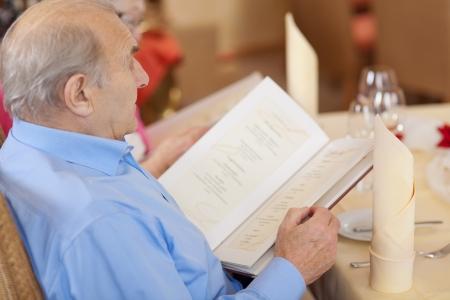 senior reading the menu at restaurant table photo