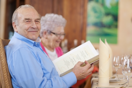 smiling senior couple in restaurant with menu in hand photo