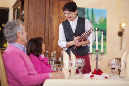 waitress and guests sitting at tablet in restaurant photo