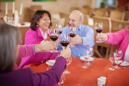 smiling seniors sitting in restaurant and drinking red wine photo