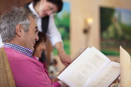 smiling guest in restaurant reading the menu with waitress in background photo