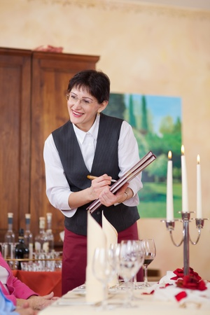 smiling waitress with menu writing the order photo