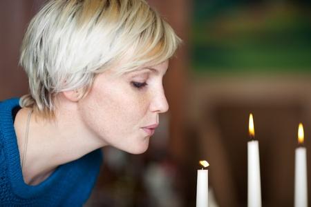 foukání: Detailní záběr na mladé ženy foukání svíčku v restauraci Reklamní fotografie