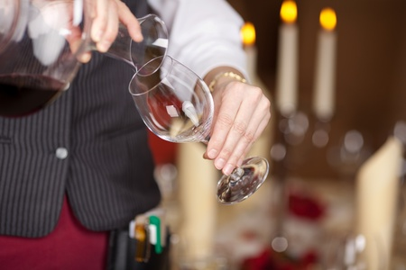 Closeup midsection of waitress pouring red wine in wineglass from decanter photo