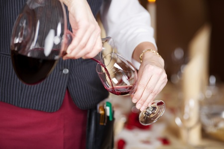 decanter: Midsection of waitress pouring red wine in wineglass from decanter
